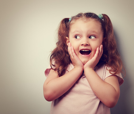 Fun surprising kid girl with open mouth looking on empty copy space. Vintage closeup portrait