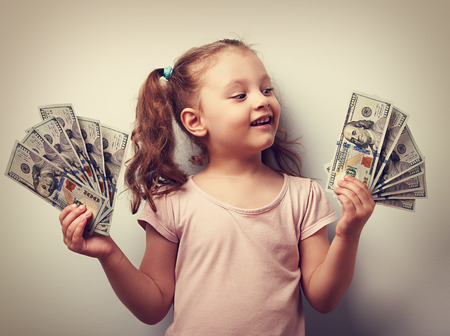 kids hand: Happy kid girl holding cash dollars and looking with smile. Vintage closeup portrait Stock Photo