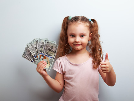 Happy rich kid girl holding money and showing thumb up sign on blue background with empty copy space Foto de archivo