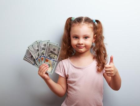 signo pesos: Feliz niña rica chico celebración de dinero y que muestra el pulgar encima de la muestra en el fondo azul con el espacio vacío de la copia