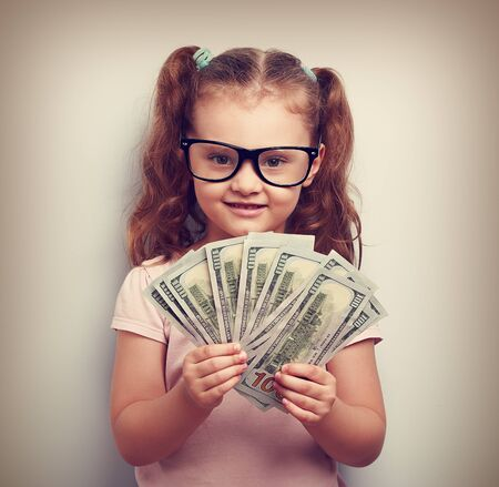 american currency: Happy kid girl in glasses holding money in the hand and looking with smile. Vintage closeup portrait