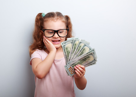 earned: Surprising emotional kid girl holding dollars in hand and thinking how much money she have earned on blue background with empty copy space