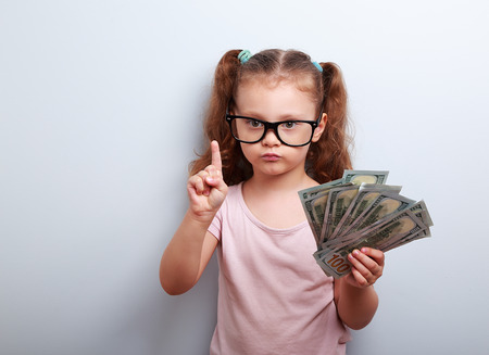 young: Cute kid girl holding dollars and have an idea how earning much money in crisis. Serious child teaching in eyeglasses