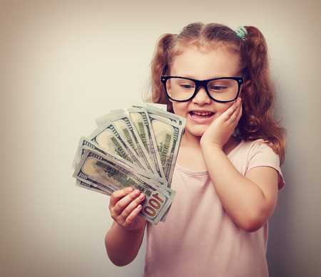 earned: Surprising emotional kid girl holding dollars in hand and thinking how much money she have earned on blue background with empty copy space.Vintage closeup portrait Stock Photo