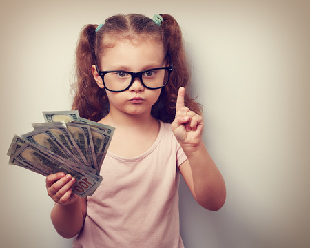 Cute kid girl holding dollars and have an idea how earning much money in crisis. Serious child teaching in eyeglasses. Vintage closeup portrait Archivio Fotografico