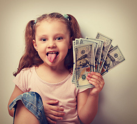 Funny small kid girl holding money and showing the tongue. Vintage closeup portrait