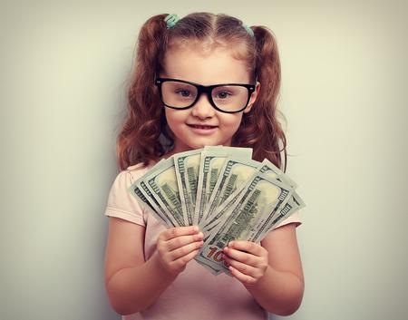 cash: Emoci�n chica Ni�o feliz en copas con dinero en la mano y mirando con una sonrisa. Vintage retrato de cerca Foto de archivo