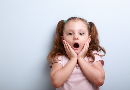surprise: Fun surprising kid girl with opened mouth looking on blue background with empty copy space
