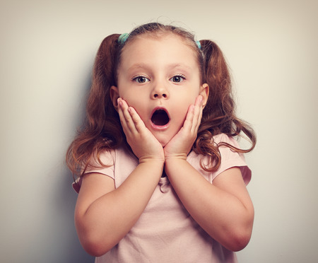 Fun surprising kid girl with opened mouth looking. Toned closeup portrait Imagens