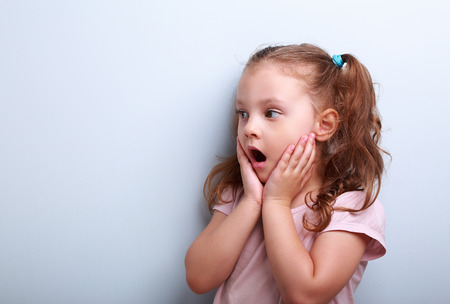 Surprising kid girl with opened mouth and hand near face looking on blue copy space background Banque d'images