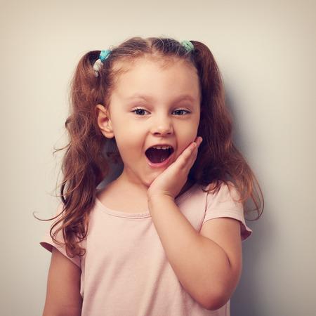 sorpresa: Chica divertida sorprendente mirando con la boca abierta. Vintage retrato de cerca