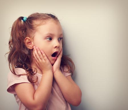 caras graciosas: Chica chico sorprendente con la boca abierta y la mano cerca de la cara mirando. Retrato virada. Acercamiento