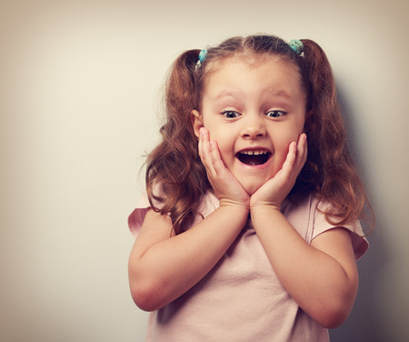 astonishment: Happy very excited kid girl with open mouth looking. Closeup vintage portrait