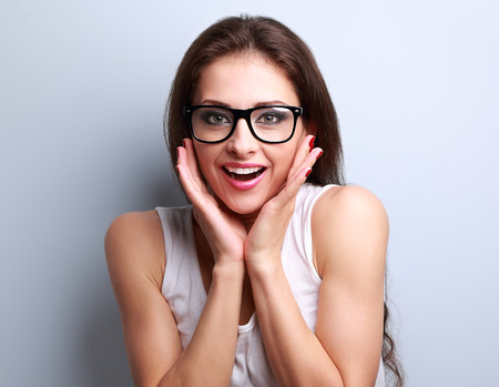 Surprised fun young woman in eye glasses with open mouth looking on blue background with empty copy space