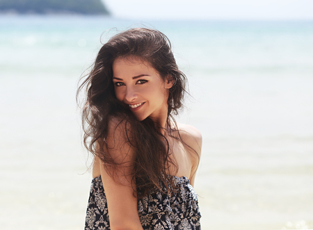 Belle femme souriante à pleines dents joying sur fond bleu, mer, fond