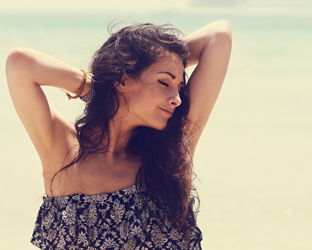 Happy beautiful closed eyes woman relaxing with epilation armpits on blue sea background. Closeup  vintage portrait