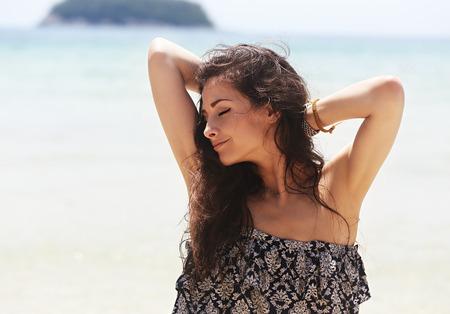 Gelukkig geniet mooie gesloten ogen vrouw met epileren oksels op blauwe zee achtergrond
