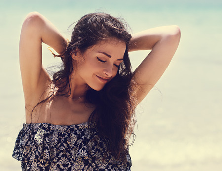armpits: Relaxing beautiful woman with closed eyes  and epilation armpits on blue sea background. Vintage closeup portrait Stock Photo