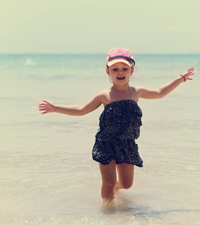 cute little girl: Happy emotional kid girl running in the blue sea in dress and very enjoying. Vintage portrait