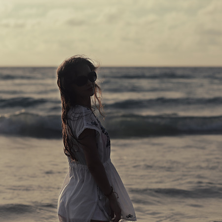 woman sunset: Beautiful woman in summer dress standing in ocean on sunset eveing background