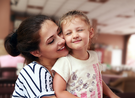 Happy mother and cute enjoying girl cuddling with love and closed eyes indoor background