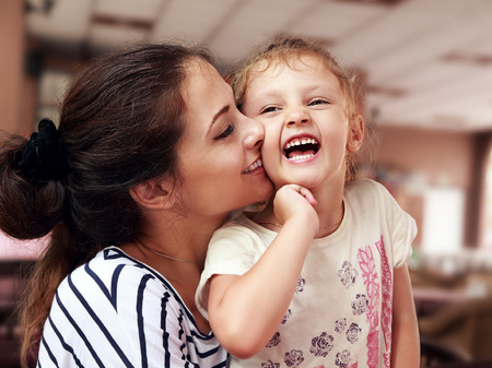 hugs and kisses: Beautiful young mother hugging her joying happy daughter indoor background Stock Photo