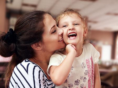 bacio: Bella giovane madre che abbraccia la sua figlia felice joying sfondo coperta