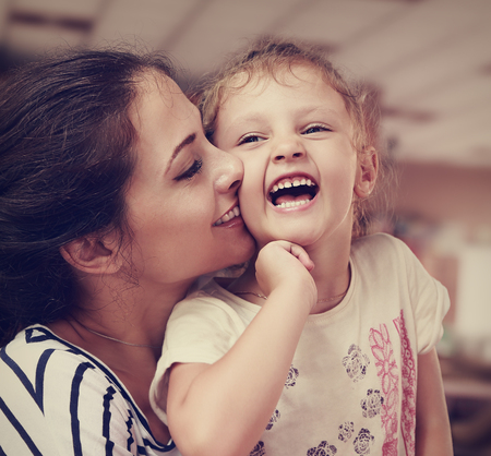 Beautiful young mother kissing her joying happy cute daughter indoor background. Closeup portrait