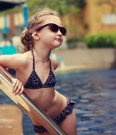 wet suit: Little female model posing in fashion kids sunglasses and swimsuit near swimming pool. Closeup portrait Stock Photo