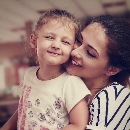 female portrait: Happy mother and cute enjoying girl cuddling with love and closed eyes indoor background. Closeup vintage portrait