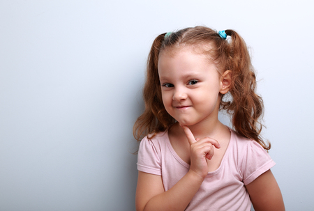 cunning: Cunning thinking small kid girl with finger near face on blue background with empty copy space Stock Photo