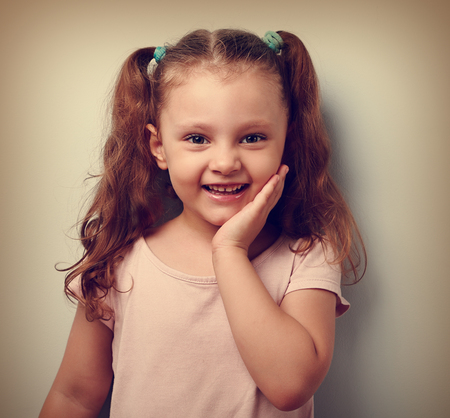 Happy emotional kid girl smiling with hand at face. Closeup vintage portrait of happiness