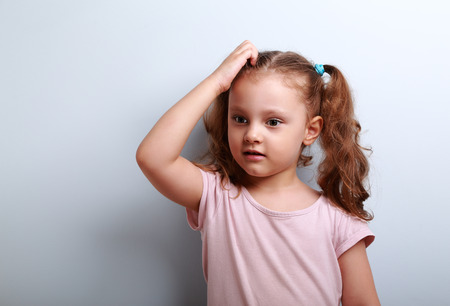 Cute thinking worried kid girl sctaching the head and looking on empty copy space blue background