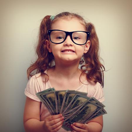 niños sonriendo: Muchacha de la diversión emocional niño pequeño en los vidrios que sostienen y que muestran dólares. Feliz ganador. Vintage retrato de cerca