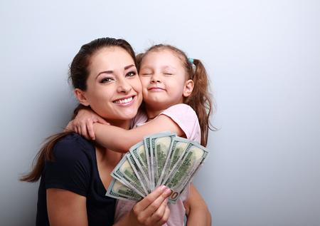 cash: Madre sonriente y feliz abrazos hija linda y mostrando dólares. Familia feliz ganadora. Retrato de detalle con el espacio vacío de la copia