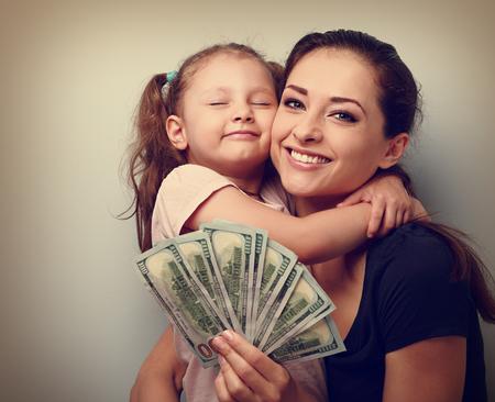 ganancias: Madre sonriente y feliz abrazos hija linda y mostrando dólares. Familia feliz ganadora. Vintage retrato de cerca Foto de archivo