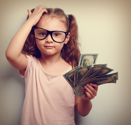 Pequeño profesor de anteojos rascarse la cabeza, la celebración de dinero y pensando cómo pendiente más. Kid tiene una gran idea. Emocional retrato de cerca la vendimia Foto de archivo