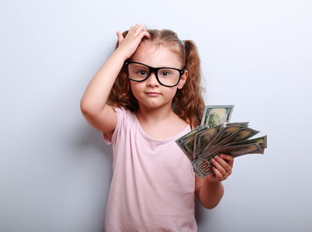 Small professor in eye glasses scratching head, holding money and thinking how earring more. Kid have an big idea. Emotional portrait on blue background with empty copy space