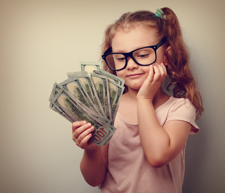 finance girl: Dreaming cute kid girl looking on money and thinking how can spend its. Closeup vintage portrait Stock Photo