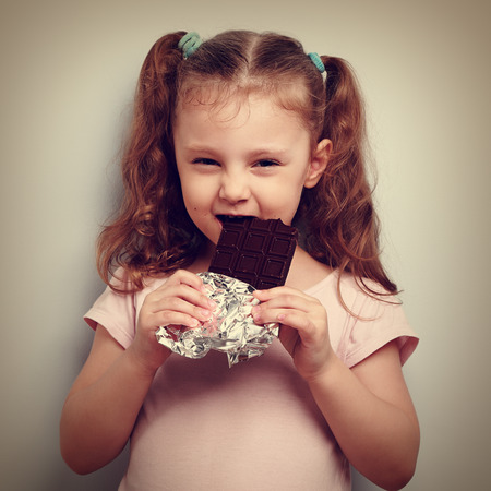 cunning: Cunning kid girl eating dark chocolate with pleasure and curious look. Vintage closeup portrait