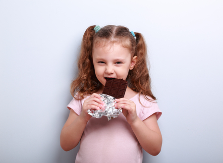 tricky: Cunning fun kid girl eating dark chocolate with curious look on blue background Stock Photo