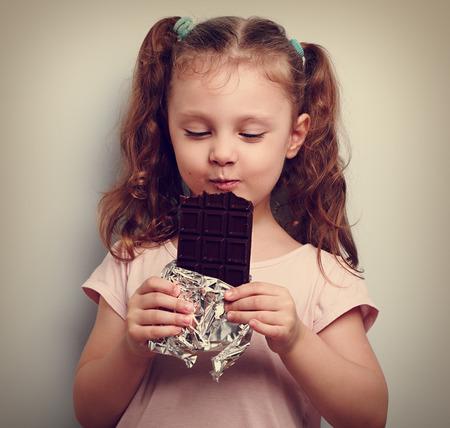 Glückliches Kind Mädchen essen Gesundheit dunkle Schokolade mit Freude und geschlossenen Augen. Weinleseportrait