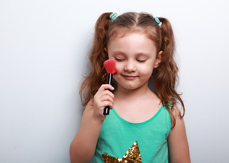 tonal: Fun beautiful small kid girl applying tonal cosmetic on the face using makeup brush with happy smile on blue background Stock Photo