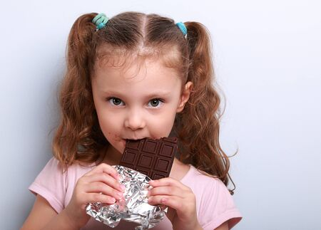 tricky: Beautiful cute kid girl eating dark healthy chocolate with fun look on blue background Stock Photo