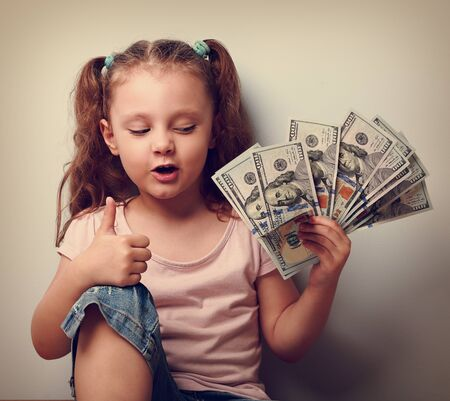 earned: Happy kid girl holding money and thinking how many dollar I earned and showing thumb up sign. Vintage portrait