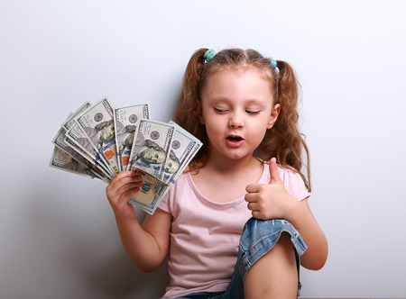 earned: Happy kid girl holding money and thinking how many dollar I earned and showing thumb up sign on blue background