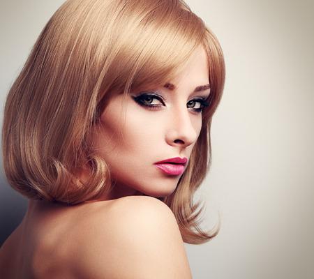 короткие волосы: Красивая женщина модель с модой блондинка прическа и зелеными глазами, глядя сексуальность. Крупным планом портрет тонированное Фото со стока