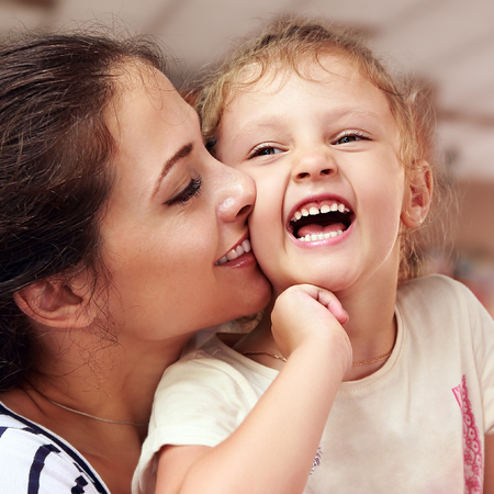 Beautiful smiling young mother hugging her joying happy daughter. Closeup portrait of people lifestyle