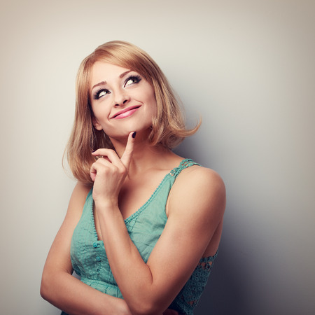 Cute thinking happy woman looking up with natural emotion and casual clothing. Portrait with empty copy space