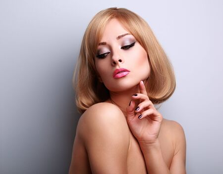 touch down: Beautiful makeup woman with perfect clean skin looking down and touching fingers the face on blue background with empty copy space
